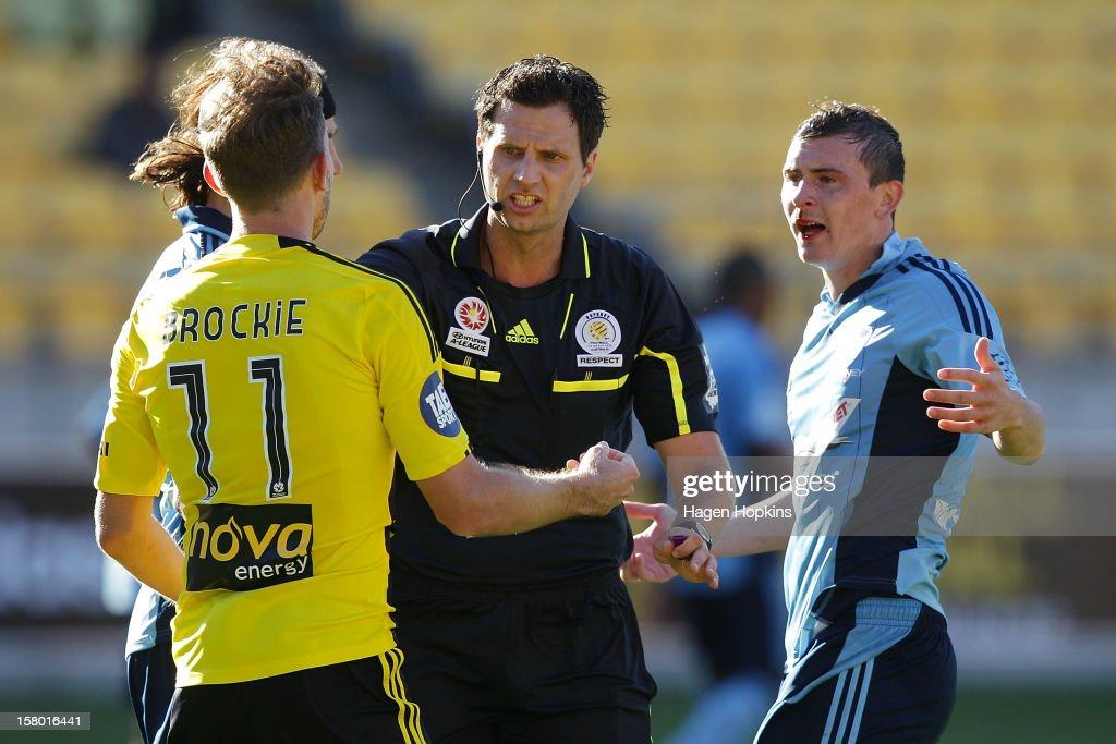 Jeremy Brockie of the Phoenix and Sebastian Ryall of Sydney FC exchange words in front of referee Kris Griffiths-Jones during the round 10 A-League match between Wellington Phoenix and Sydney FC at Westpac Stadium on December 9, 2012 in Wellington, New Zealand.