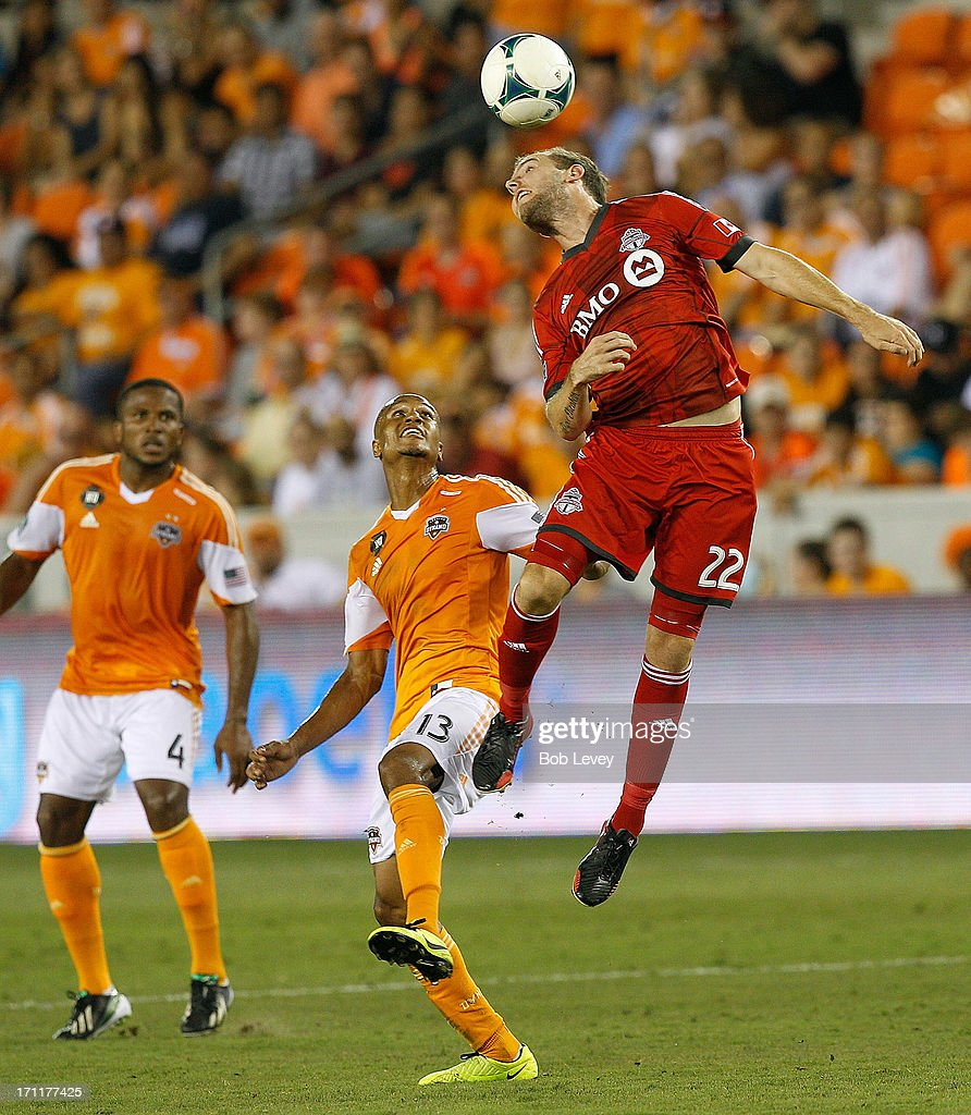 Jeremy Brockie #22 of the Toronto FC heads the ball away from Ricardo Clark #13 of Houston Dynamo in the second half at BBVA Compass Stadium on June 22, 2013 in Houston, Texas.