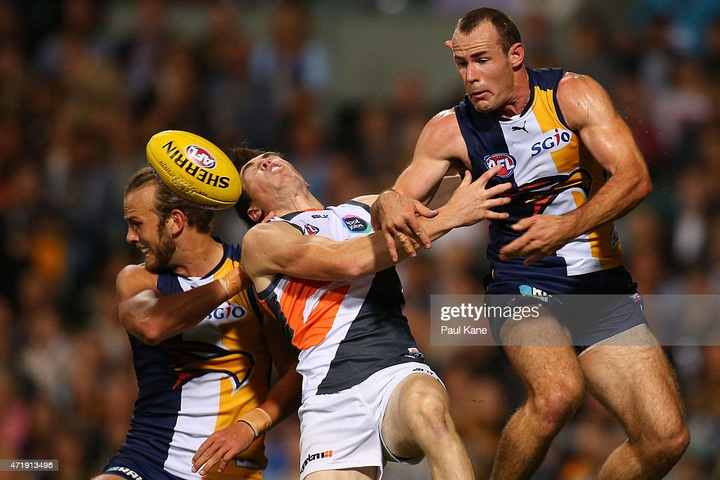 Jeremy Cameron of the Giants is struck high in marking contest for the ball against Will Schofield and Shannon Hurn of the Eagles during the round...