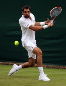 Jeremy Chardy of France plays a backhand during his Gentlemen's Singles first round match against Daniel Cox of Great Britain on day one of the...