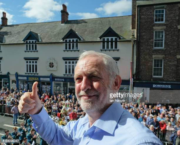 Jeremy Corbyn leader of the Labour Party gives a thumbs up as he stands on the balcony of the County Hotel as colliery bands pass below during the...