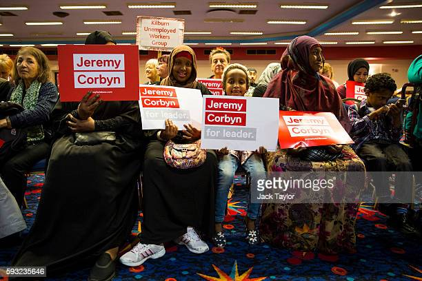 Jeremy Corbyn supporters hold placards as they sit in the audience during a rally for the Labour leader at Ruach City Church in Kilburn on August 21...