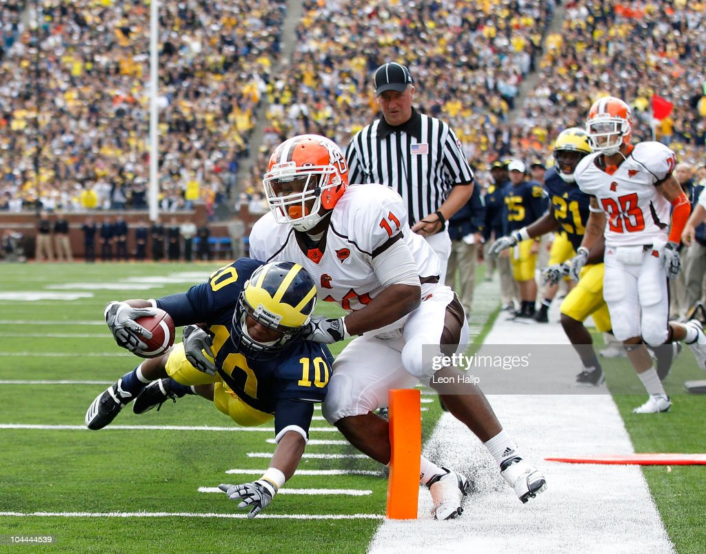 Jeremy Gallon of the Michigan Wolverines runs 11 yards for a first quarter touchdown as Jovan Leacock of Bowling Green attempts to make the stop on...