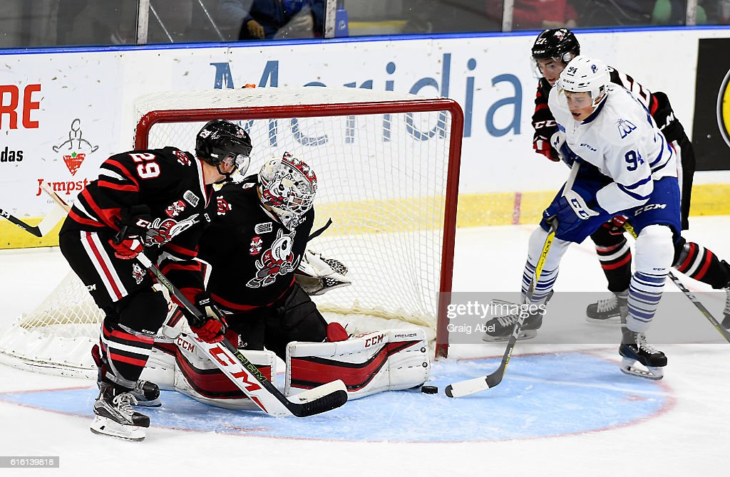 Jeremy Goodwin #94 of the Mississauga Steelheads slides in a rebound for a goal against Colton Incze #31 and Laim Harn #29 of the Niagara IceDogs during game action on October 21, 2016 at Hershey Centre in Mississauga, Ontario, Canada.