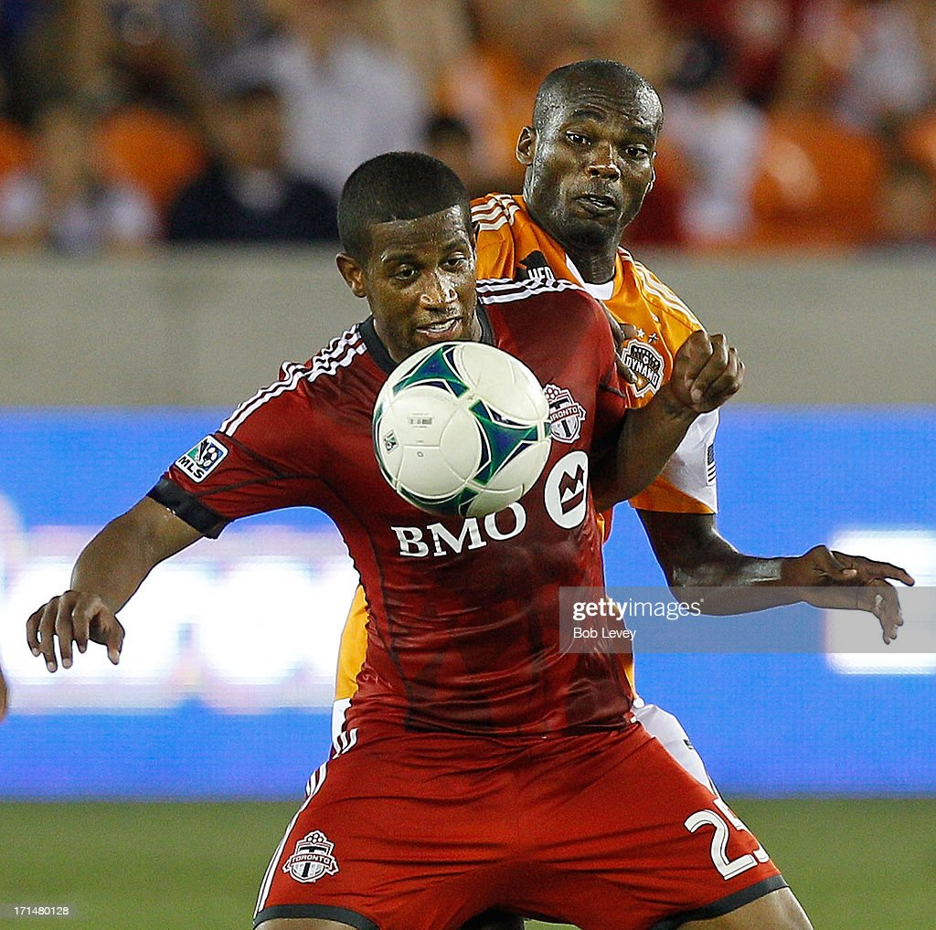 Jeremy Hall of Toronto FC and Omar Cummings during game action at BBVA Compass Stadium on June 22 2013 in Houston Texas