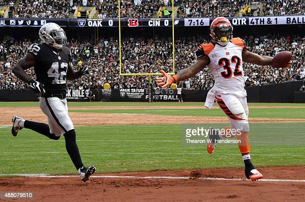 Jeremy Hill of the Cincinnati Bengals runs past Larry Asante of the Oakland Raiders to score during the first half of their NFL game at Oco Coliseum...