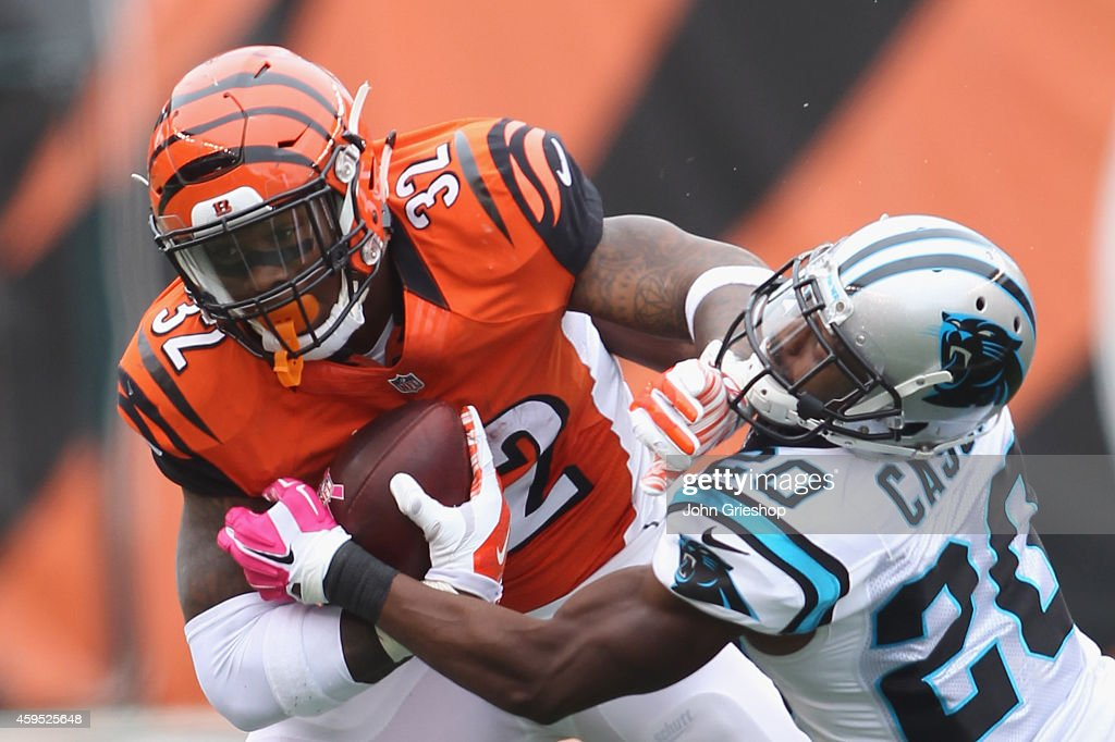 Jeremy Hill #32 of the Cincinnati Bengals runs the football upfield against <a gi-track='captionPersonalityLinkClicked' href=/galleries/search?phrase=Antoine+Cason&family=editorial&specificpeople=2803078 ng-click='$event.stopPropagation()'>Antoine Cason</a> #20 of the Carolina Panthers during their game at Paul Brown Stadium on October 12, 2014 in Cincinnati, Ohio. The Bengals and the Panthers 37-37.