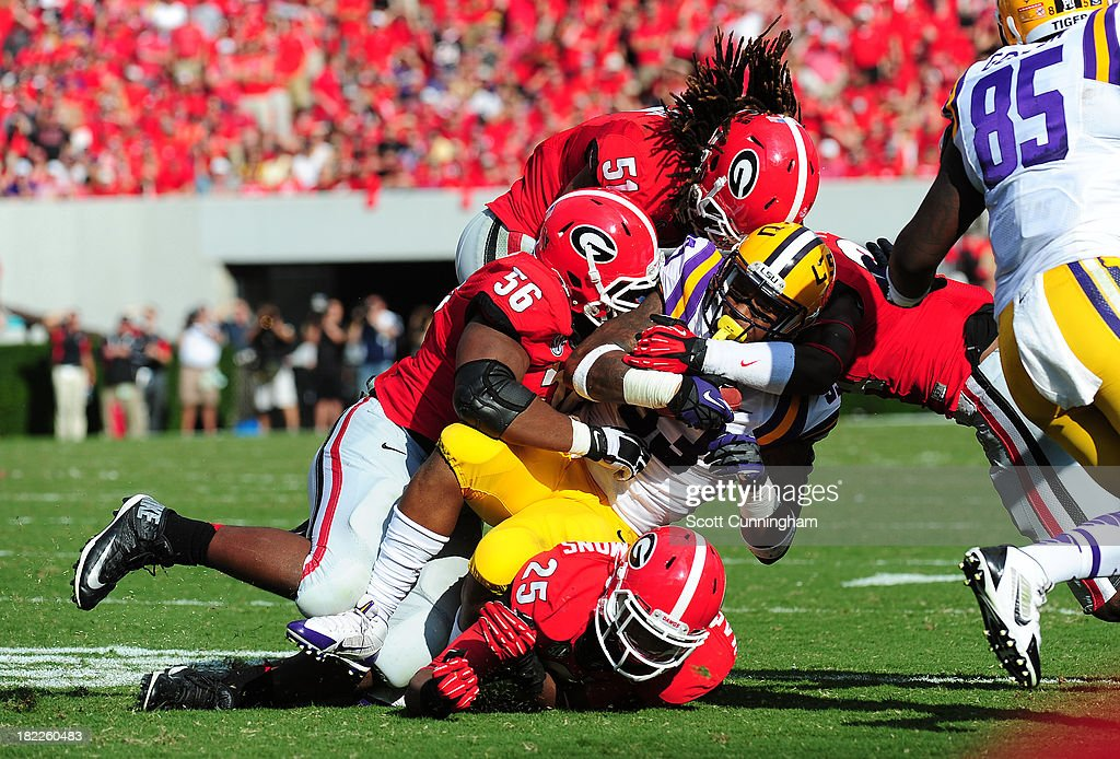 Jeremy Hill #33 of the LSU Tigers is tackled by Josh Harvey-Clemons #25, Garrison Smith #56, and Ramik Wilson #51 of the Georgia Bulldogs at Sanford Stadium on September 28, 2013 in Athens, Georgia.