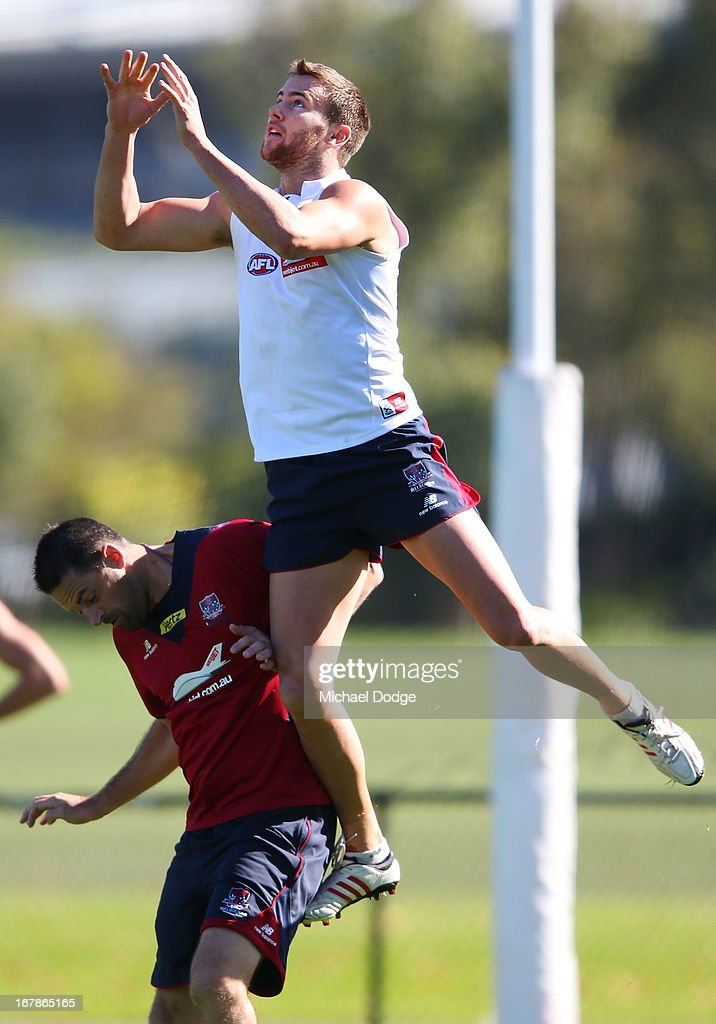 Jeremy Howe jumps to mark the ball over assistant coach <a gi-track='captionPersonalityLinkClicked' href=/galleries/search?phrase=Jade+Rawlings&family=editorial&specificpeople=217803 ng-click='$event.stopPropagation()'>Jade Rawlings</a> during a Melbourne Demons AFL training session at Gosch's Paddock on May 2, 2013 in Melbourne, Australia.