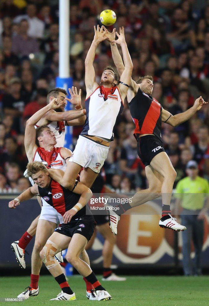 Jeremy Howe of the Demons jumps for a high mark over Michael Hurley of the Bombers but drops the ball during the round two AFL match between the Essendon Bombers and the Melbourne Demons at Melbourne Cricket Ground on April 6, 2013 in Melbourne, Australia.