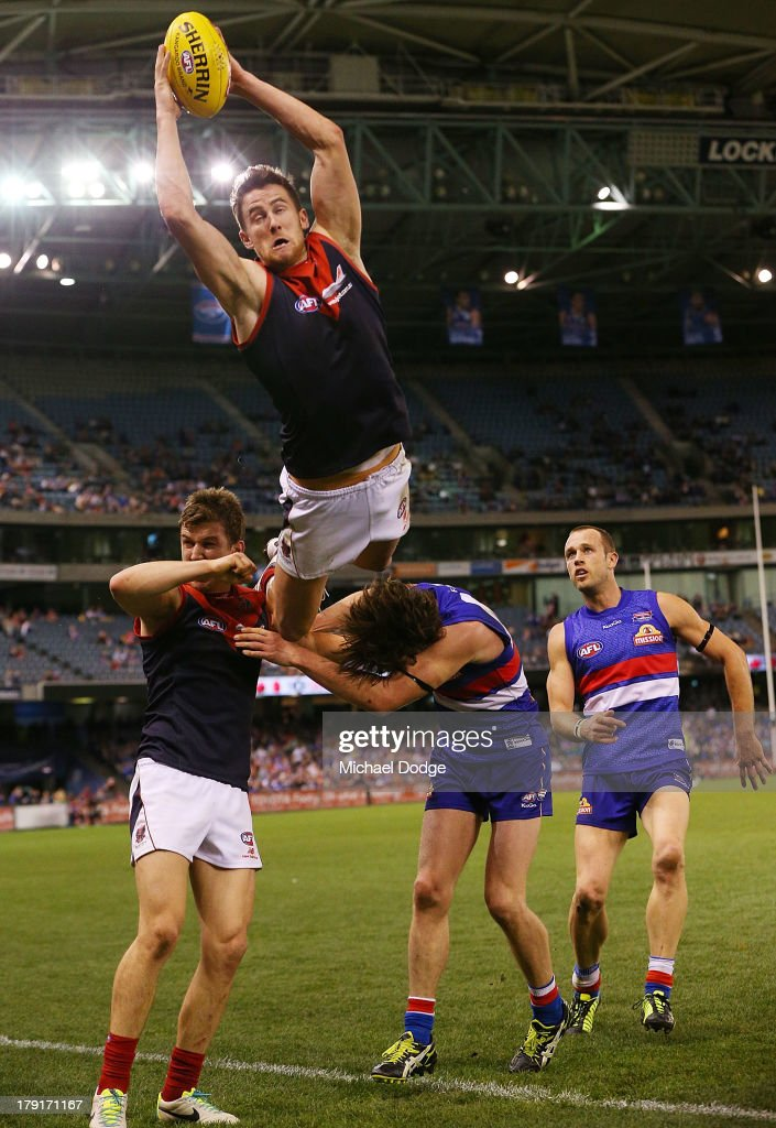Jeremy Howe of the Demons marks the ball high over Jack Trengove and Liam Picken of the Bulldogs during the round 23 AFL match between the Western Bulldogs and the Melbourne Demons at Etihad Stadium on September 1, 2013 in Melbourne, Australia.