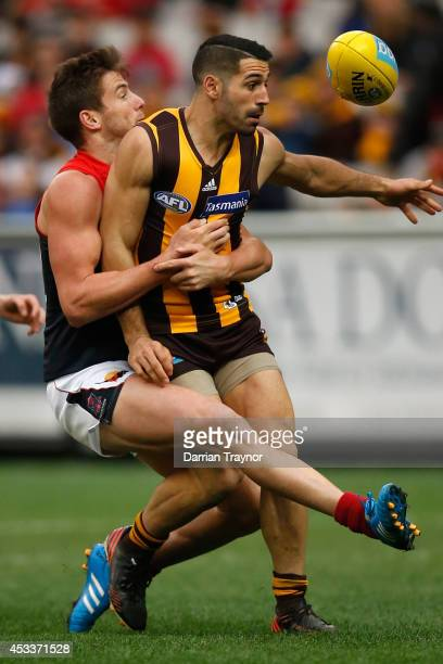 Jeremy Howe of the Demons tackles Paul Puopolo of the Hawks during the round 20 AFL match between the Hawthorn Hawks and the Melbourne Demons at...