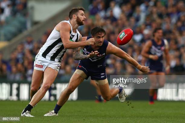 Jeremy Howe of the Magpies handballs against Shane Kersten of the Dockers during the round 11 AFL match between the Fremantle Dockers and the...