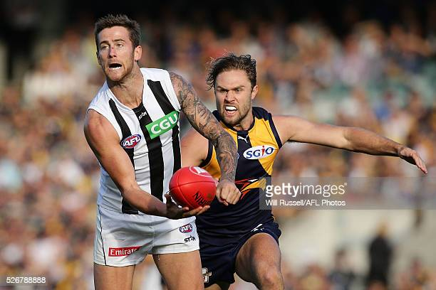 Jeremy Howe of the Magpies handballs under pressure from Mark Hutchings of the Eagles during the round six AFL match between the West Coast Eagles...