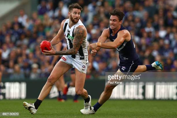 Jeremy Howe of the Magpies looks to handball against Shane Kersten of the Dockers during the round 11 AFL match between the Fremantle Dockers and the...