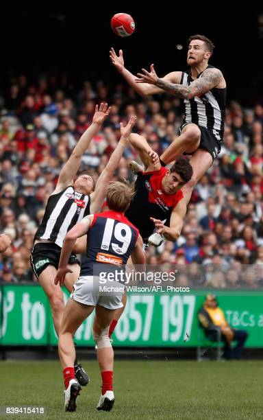 Jeremy Howe of the Magpies takes a spectacular mark over Christian Petracca of the Demons during the 2017 AFL round 23 match between the Collingwood...