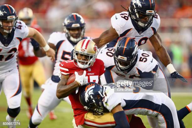 Jeremy Kerley of the San Francisco 49ers is tackled by Zaire Anderson and Justin Simmons of the Denver Broncos on a punt return at Levi's Stadium on...