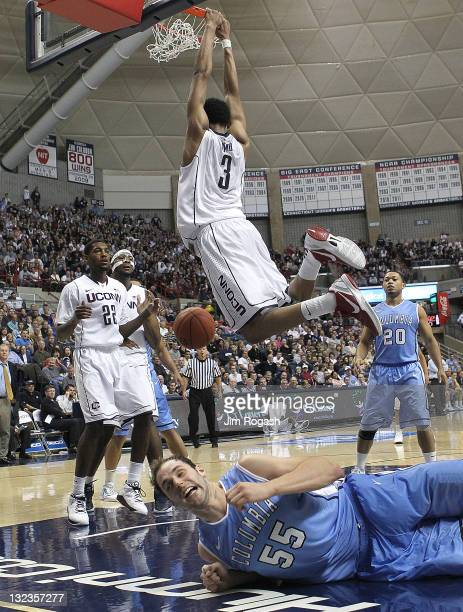 Jeremy Lamb of the Connecticut Huskies dunks the ball as Mark Cisco of the Columbia Lions reacts after he was kneed in the face in the second half at...