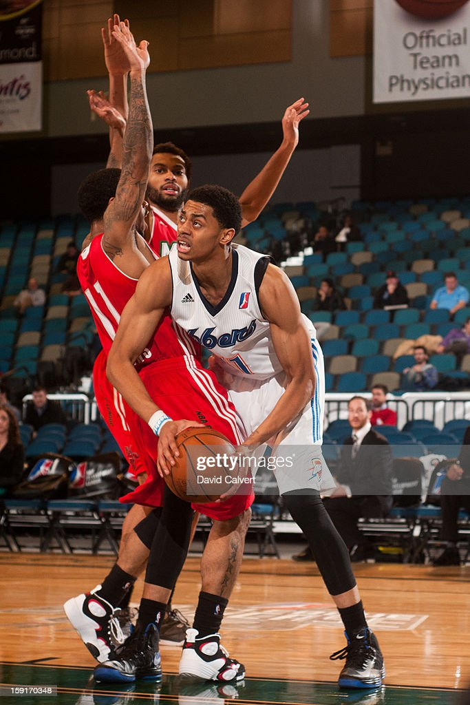 Jeremy Lamb #11 of the Tulsa 66ers drives into defenders Hank Thorns #11 and Xavier Silas #13 of the Maine Red Claws during the 2013 NBA D-League Showcase on January 7, 2013 at the Reno Events Center in Reno, Nevada.