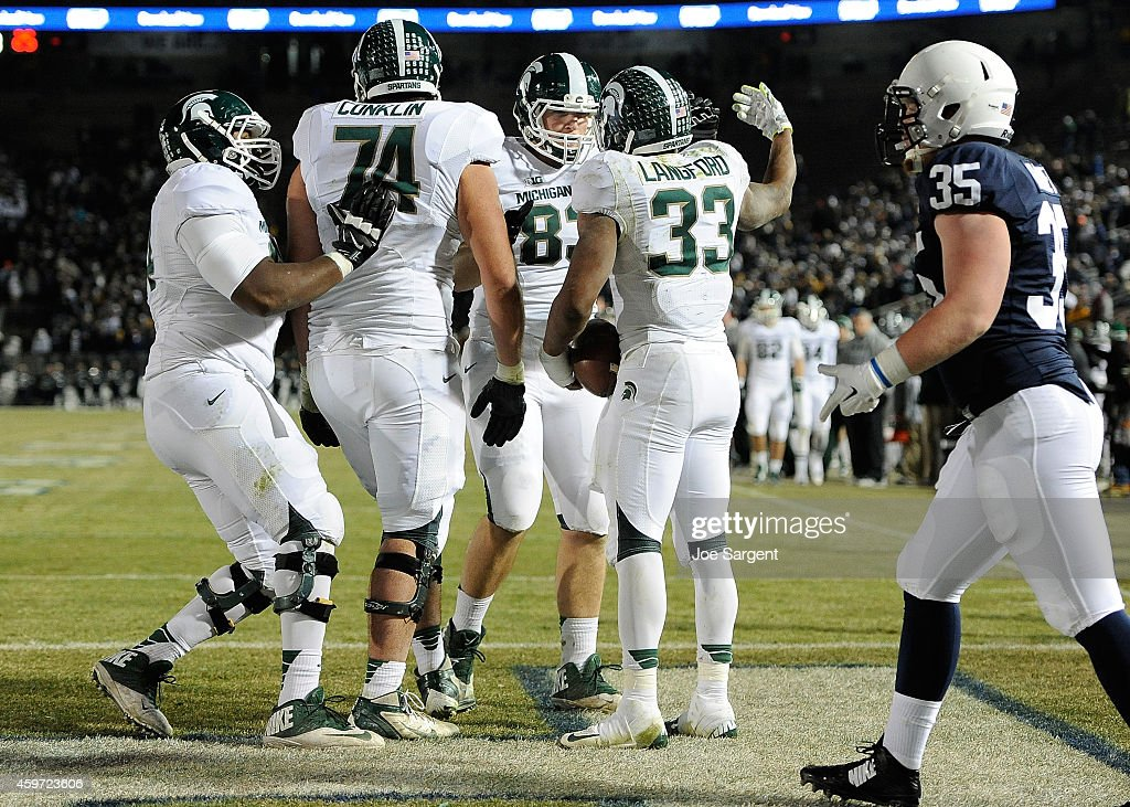Jeremy Langford of the Michigan State Spartans celebrates his fourth quarter touchdown with teammates in front of Matthew Baney of the Penn State...