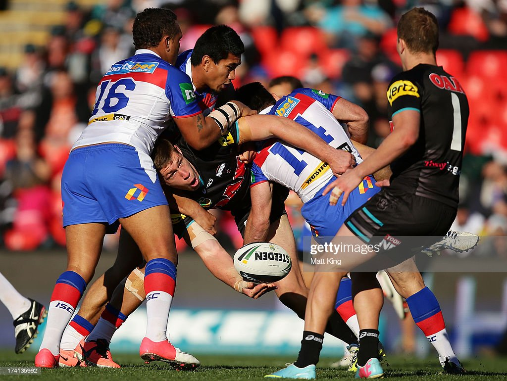 Jeremy Latimore of the Panthers offloads in a tackle during the round 19 NRL match between the Penrtih Panthers and the Newcastle Knights at Centrebet Stadium on July 21, 2013 in Penrith, Australia.