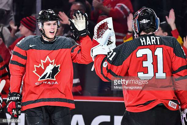 Jeremy Lauzon of Team Canada highfives goaltender Carter Hart after scoring a goal during the 2017 IIHF World Junior Championship gold medal game...