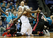 Jeremy Lin of the Charlotte Hornets battles for a loose ball against teammates Luol Deng and Josh Richardson of the Miami Heat during game four of...