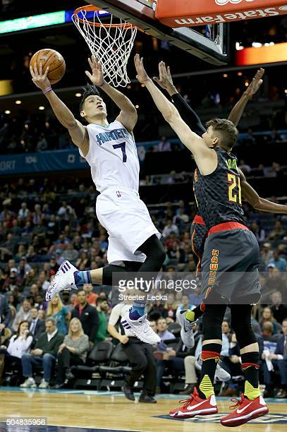 Jeremy Lin of the Charlotte Hornets drives to the basket against Kyle Korver of the Atlanta Hawks during their game at Time Warner Cable Arena on...