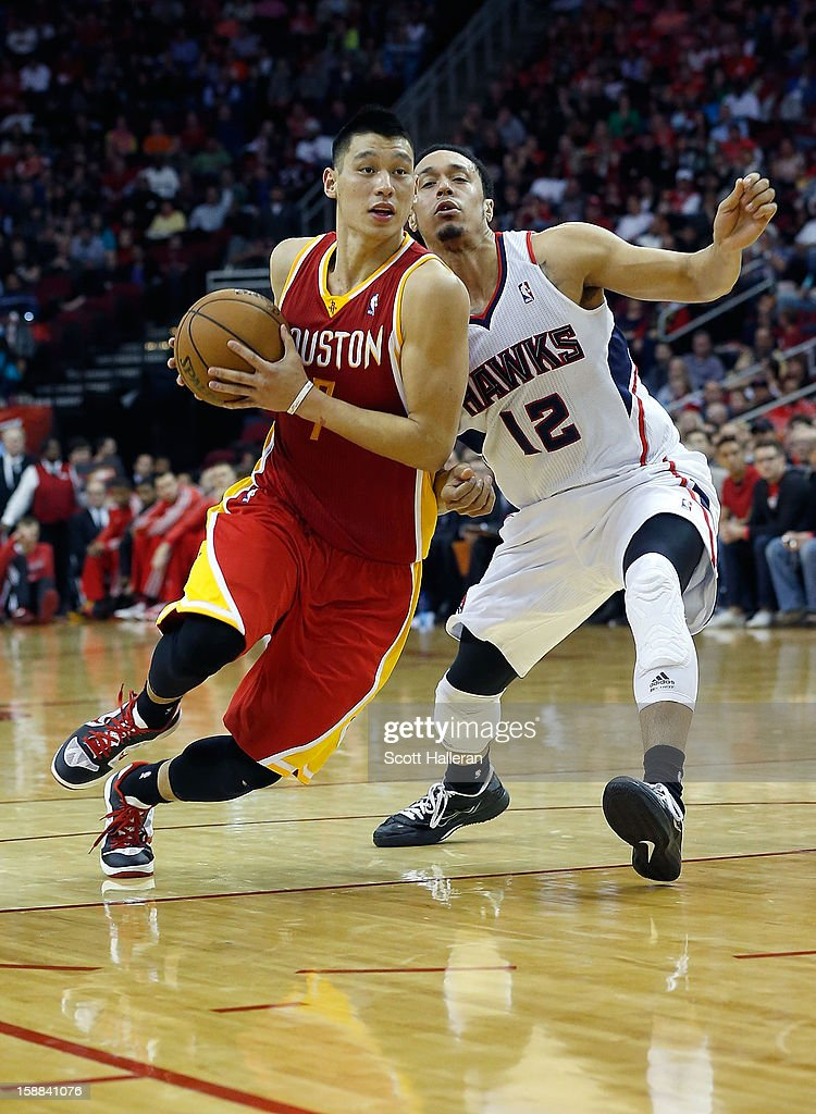 Jeremy Lin #7 of the Houston Rockets dribbles past John Jenkins #12 of the Atlanta Hawks at the Toyota Center on December 31, 2012 in Houston, Texas.