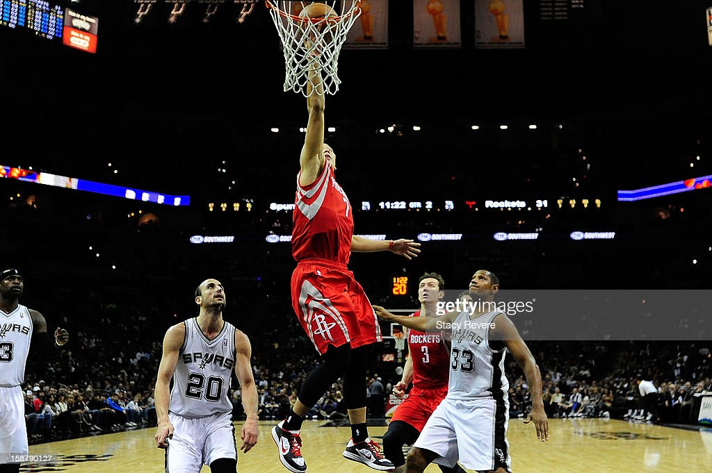 Jeremy Lin #7 of the Houston Rockets drives between Manu Ginobili #20 and Boris Diaw #33 of the San Antonio Spurs during a game at AT&T Center on December 28, 2012 in San Antonio, Texas.