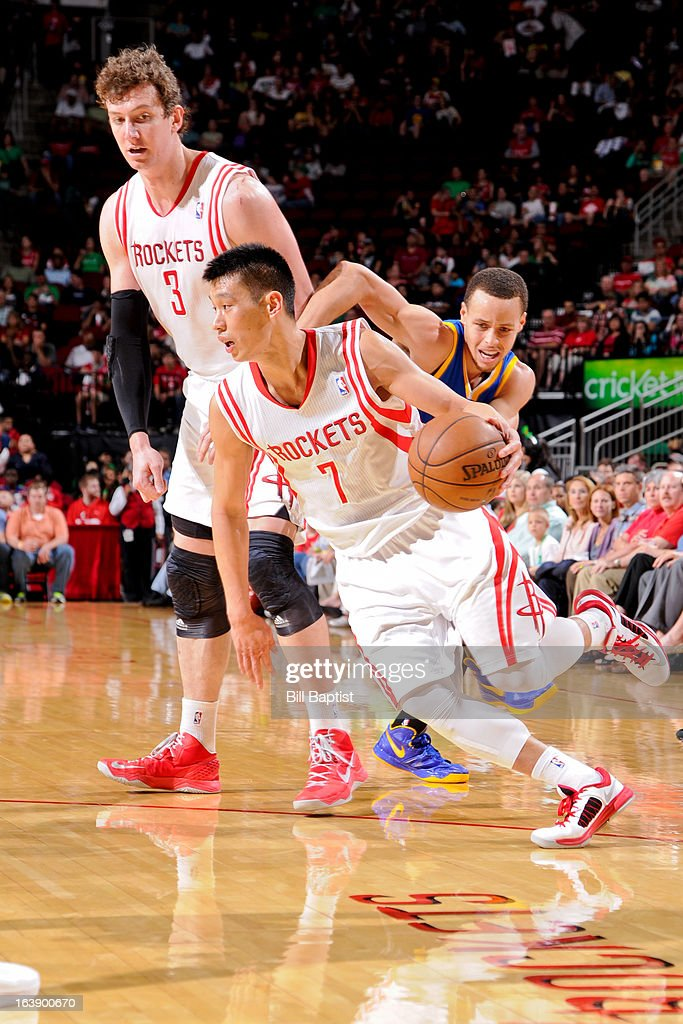 Jeremy Lin #7 of the Houston Rockets drives on a screen by teammate Omer Asik #3 against Stephen Curry #30 of the Golden State Warriors on March 17, 2013 at the Toyota Center in Houston, Texas.