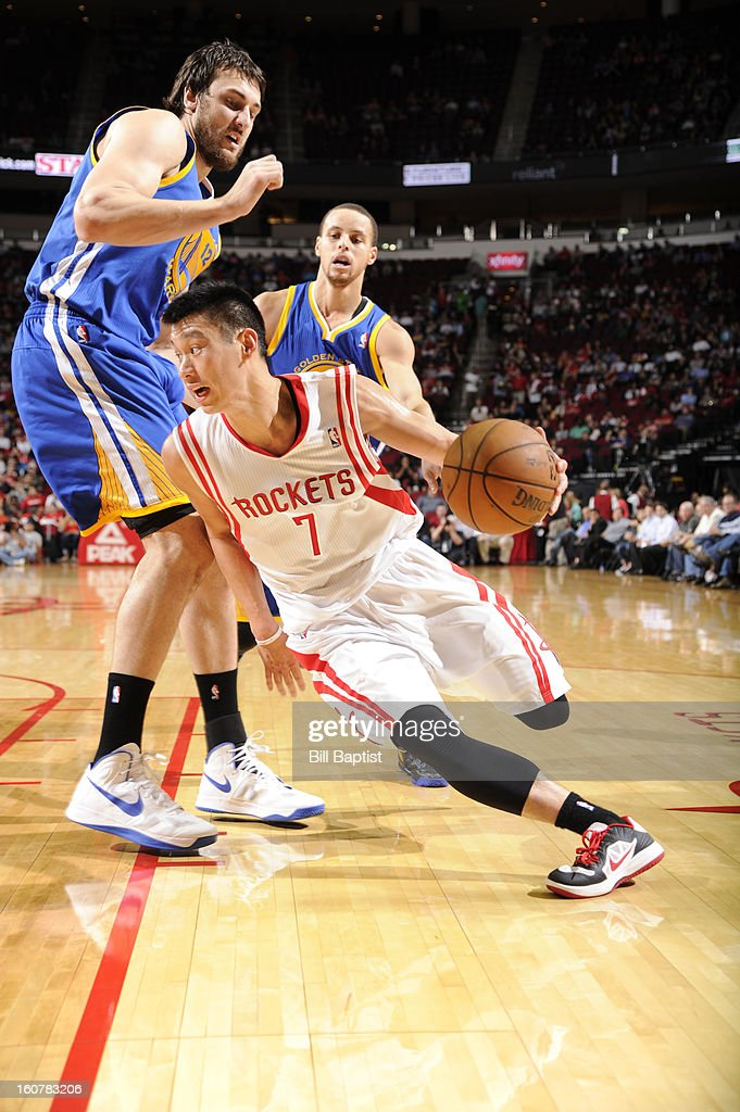 Jeremy Lin #7 of the Houston Rockets drives to the basket against Andrew Bogut #12 of the Golden State Warriors on February 5, 2013 at the Toyota Center in Houston, Texas.
