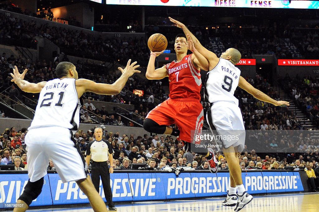 Jeremy Lin #7 of the Houston Rockets is defended by Tony Parker #9 and Tim Duncan #21 of the San Antonio Spurs during a game at AT&T Center on December 28, 2012 in San Antonio, Texas. San Antonio won the game 122-116.