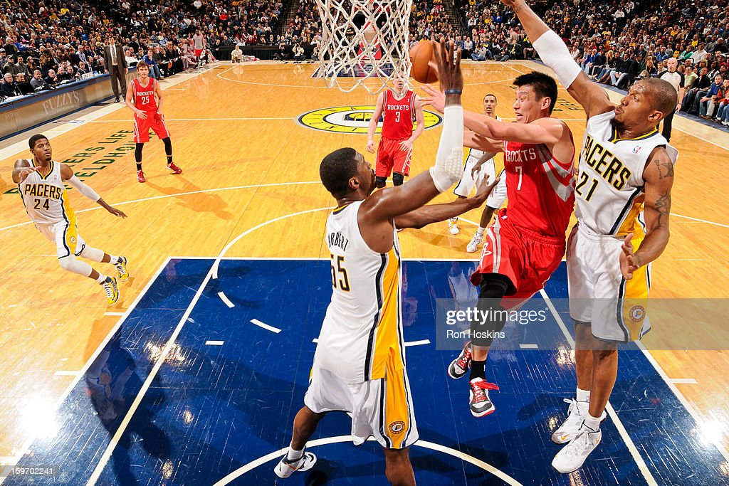 Jeremy Lin #7 of the Houston Rockets passes the ball under the basket against David West #21 and Roy Hibbert #55 of the Indiana Pacers on January 18, 2013 at Bankers Life Fieldhouse in Indianapolis, Indiana.