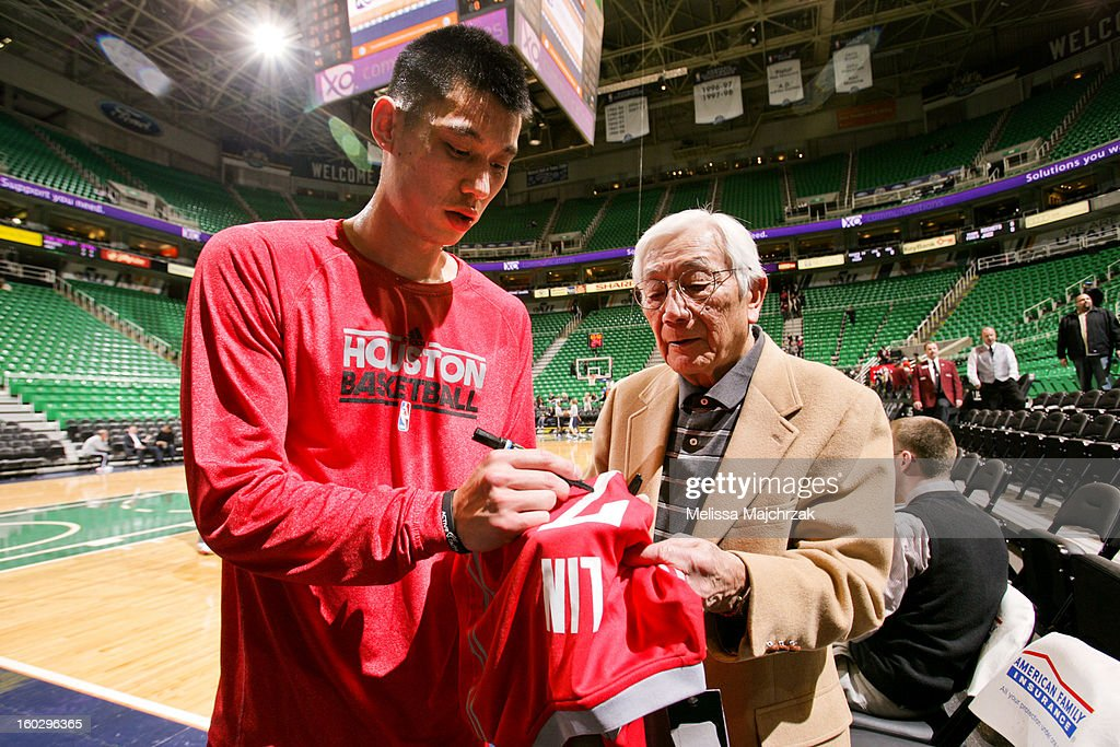 Jeremy Lin #7 of the Houston Rockets signs a shirt for Wataru Misaka, the first NBA player of Asian descent, before his game against the Utah Jazz at Energy Solutions Arena on January 28, 2013 in Salt Lake City, Utah.