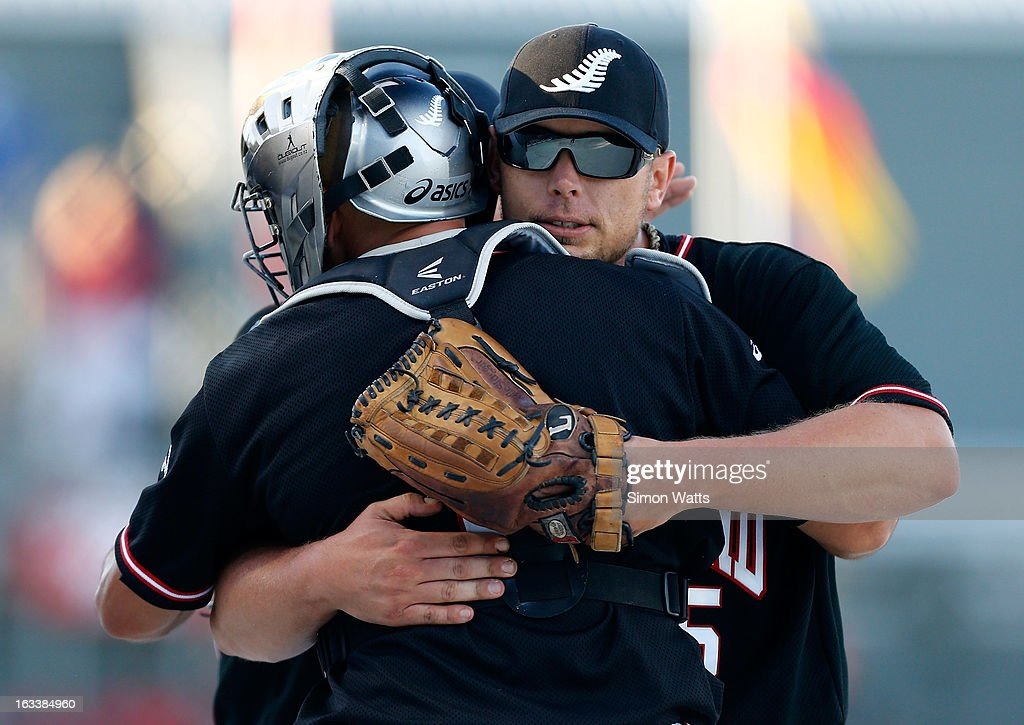 Jeremy Manley of New Zealand is embraced by catcher Patrick Shannon after New Zealand beat Venezula to make the final during the playoff match between New Zealand and Venezuela at Tradstaff Sports Stadium on March 9, 2013 in Auckland, New Zealand.