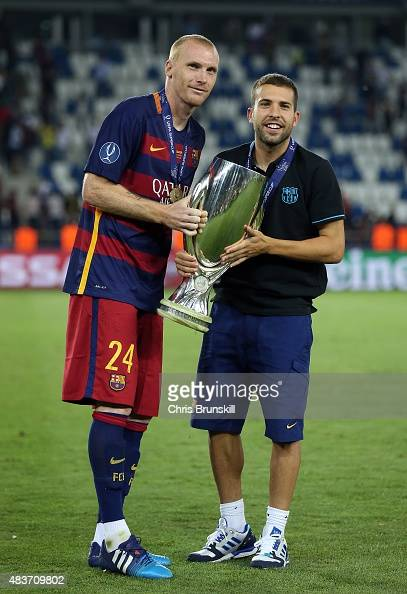 Jeremy Mathieu and Jordi Alba of Barcelona pose with the trophy following the UEFA Super Cup match between Barcelona and Sevilla FC at Dinamo Stadium...
