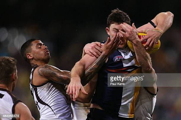 Jeremy McGovern of the Eagles gets tackled by Bradley Hill and Liam Shiels of the Hawks during the round 19 AFL match between the West Coast Eagles...