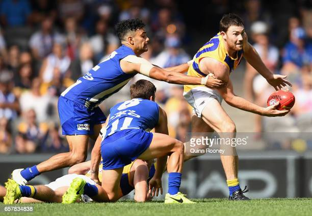 Jeremy McGovern of the Eagles handballs whilst being tackled by Lindsay Thomas of the Kangaroos during the round one AFL match between the North...