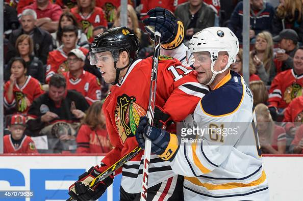 Jeremy Morin of the Chicago Blackhawks and Andre Benoit of the Buffalo Sabres watch for the puck during the NHL game on October 11 2014 at the United...