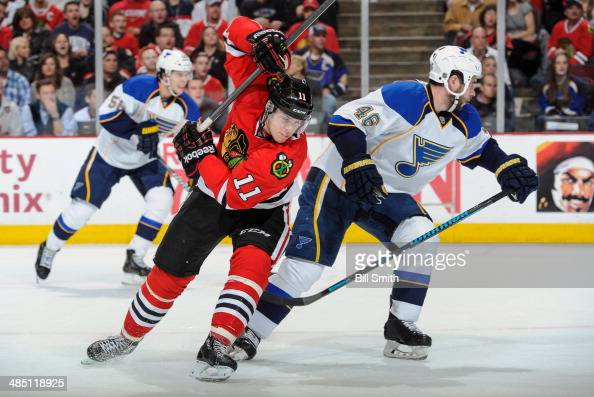 Jeremy Morin of the Chicago Blackhawks and Roman Polak of the St Louis Blues skate during the NHL game on April 6 2014 at the United Center in...