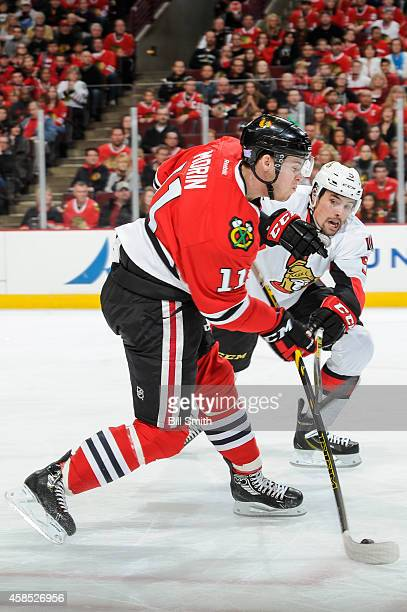 Jeremy Morin of the Chicago Blackhawks hits the puck past Cody Ceci of the Ottawa Senators during the NHL game on October 26 2014 at the United...