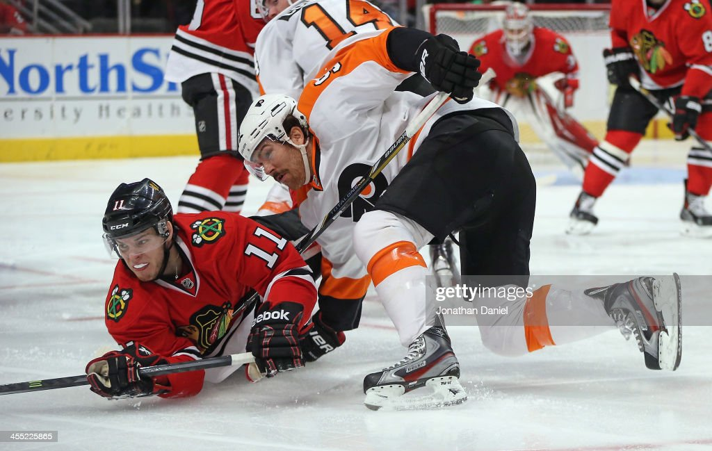 Jeremy Morin #11 of the Chicago Blackhawks is knocked to the ice by <a gi-track='captionPersonalityLinkClicked' href=/galleries/search?phrase=Steve+Downie&family=editorial&specificpeople=714514 ng-click='$event.stopPropagation()'>Steve Downie</a> #9 of the Philadelphia Flyers at the United Center on December 11, 2013 in Chicago, Illinois.