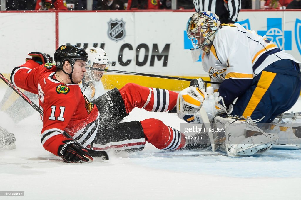 Jeremy Morin of the Chicago Blackhawks slides into goalie Pekka Rinne of the Nashville Predators during the NHL game on March 23 2014 at the United...