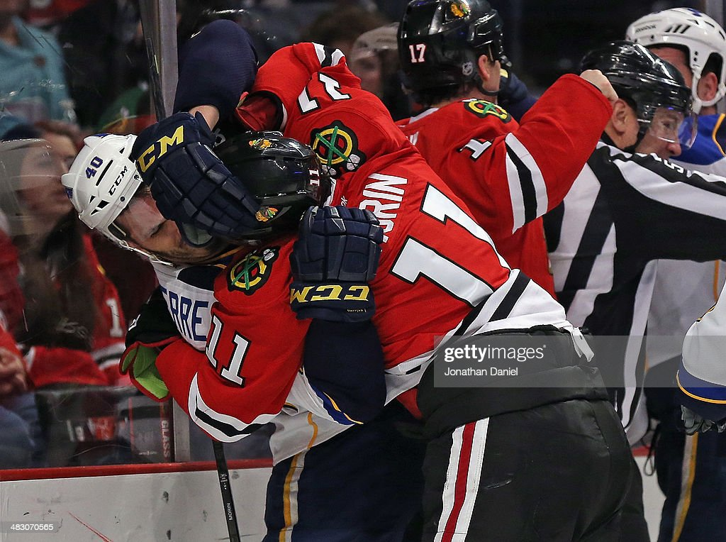 Jeremy Morrin #11 of the Chicago Blackhawks tangles with Maxim Lapierre #40 of the St. Louis Blues at the United Center on April 6, 2014 in Chicago, Illinois.