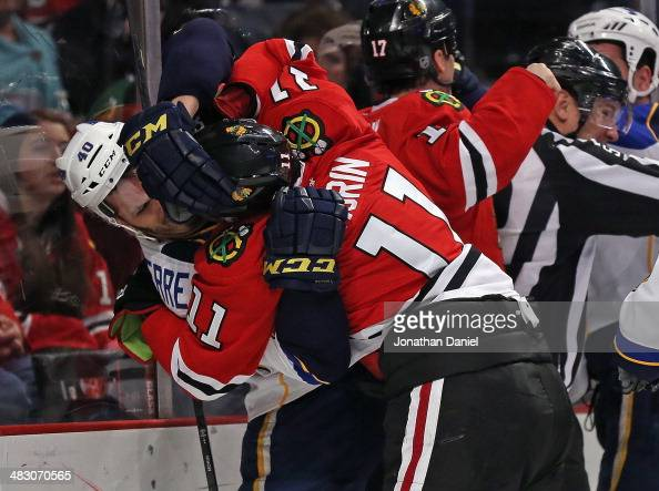 Jeremy Morrin of the Chicago Blackhawks tangles with Maxim Lapierre of the St Louis Blues at the United Center on April 6 2014 in Chicago Illinois