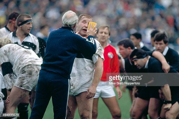 Jeremy Pugh of Neath is sponged by a physio after being punched in the face by Steve McDowall of the New Zealand All Blacks during the rugby union...