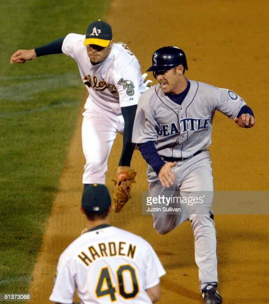 Jeremy Reed of the Seattle Mariners is tagged out by Bobby Crosby of the Oakland Athletics as he gets caught in a rundown September 29 2004 at the...