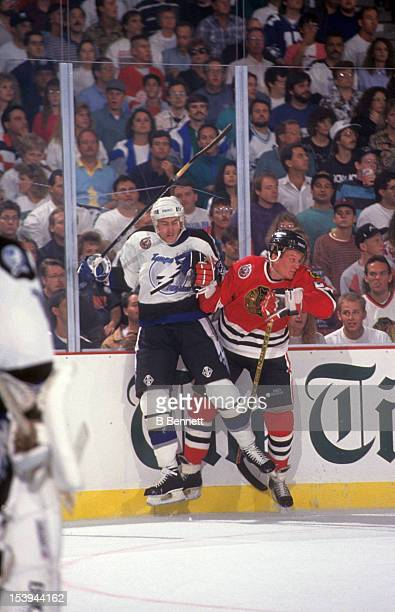 Jeremy Roenick of the Chicago Blackhawks checks Roman Hamrlik of the Tampa Bay Lightning into the boards during an NHL game circa 1993 at the Expo...