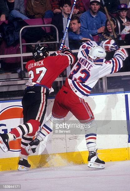 Jeremy Roenick of the Chicago Blackhawks checks Tony Amonte of the New York Rangers into the boards during an NHL game circa 1993 at the Madison...